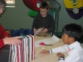 Jonathan and Andy wrapping gifts with Vivian\'s help